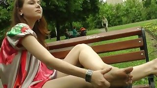 Sexy young teen shows her perfect tiny legs feet and toes in the park